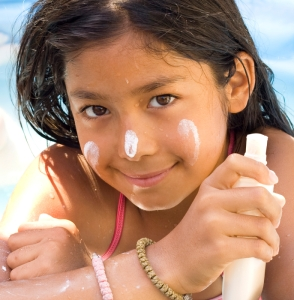 Young girl using sunscreen