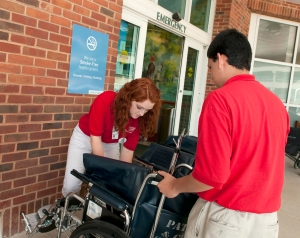 UVA Health System Junior Volunteers Micaela Miller and Adam Ladd adjust a wheelchair outside the Emergency Department.